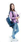 Full length portrait of a smiling young woman. Standing with backpack and tablet computer. Looking at camera Stock Image