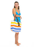 Full length portrait of smiling woman in swimsuit. Full length portrait of smiling young woman in swimsuit with beach bag Stock Photography