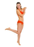 Full length portrait of smiling young woman in swimsuit Royalty Free Stock Image