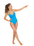 Full length portrait of smiling woman in swimsuit. Full length portrait of smiling young woman in swimsuit pointing on copy space Stock Photo