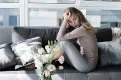 Sad lady locating on couch. Full length portrait of sorrowful young woman sitting on comfortable sofa in living room. Sorrow concept Royalty Free Stock Images