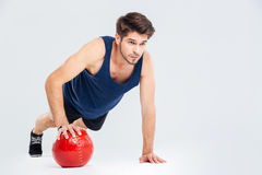 Full length portrait of a sportsman workout with fitness ball. Full length portrait of a sports man workout with fitness ball isolated on a gray background Stock Photography