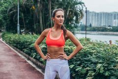 Full-length portrait of sporty fit model standing in park posing in pink sports bra and white leggings with hands on royalty free stock image