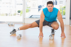 Full length portrait of a sporty man doing stretching exercise. In fitness studio royalty free stock photography