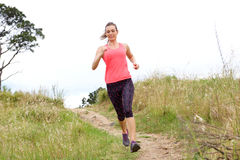 Full length portrait of sporty woman running on dirt path. Outdoors in park stock photography
