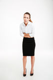 Full length portrait of a stressed businesswoman having stomach pain. Over white background Royalty Free Stock Images