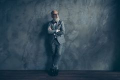 Full length portrait of stunning perfect brutal harsh old man in. Suit with bow, having hands crossed, leg by foot standing on wooden floor over gray wall Royalty Free Stock Image
