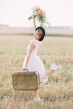 The full-length portrait of the stylish bride carrying the vintage suitcaise and keeping up the colourful bouquet in the Royalty Free Stock Photography