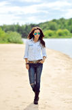 Full length portrait of stylish woman walking on a beach Royalty Free Stock Image