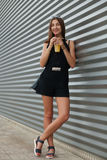 Full length portrait of stylish young beautiful hipster woman in little black dress drinking lemonade outdoors Stock Image