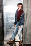 Full length portrait of stylish young fashion model man in bright red sunglasses and denim casual style posing near metallic door. Lean and looking away royalty free stock photo