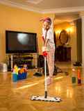 Full length portrait of teen girl washing wooden floor with swab Royalty Free Stock Images