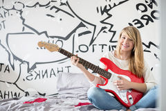 Full-length portrait of teenage girl playing guitar in bedroom Royalty Free Stock Image