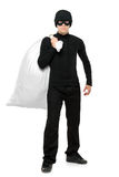 Full length portrait of a thief holding a bag. Isolated against white background Stock Image