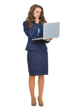Full length portrait of thoughtful business woman with laptop Royalty Free Stock Photos