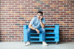 Full length portrait of thoughtful serious handsome young bearded man in casual style and eyeglasses sitting on blue wooden pallet royalty free stock images