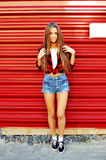 Full length portrait of trendy hipster girl standing at the red. Wall background Royalty Free Stock Images
