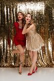Full length portrait of two beautiful playful women. In sparkly dresses standing and blowing a kiss isolated over golden shiny background Stock Photo