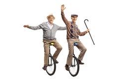 Two cheerful senior men riding unicycles stock photo