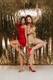 Full length portrait of two cheery girls in shiny dresses Stock Photos