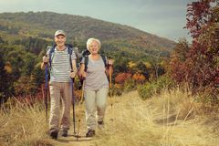 Two elderly hikers walking towards the camera outdoors. Full length portrait of two elderly hikers walking towards the camera outdoors Stock Images