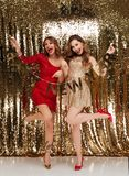 Full length portrait of two excited smiling women. In sparkly dresses looking at camera while standing and holding happy new year ribbon isolated over golden royalty free stock images