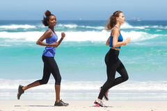 Full length portrait of two fit young women running on beach. Full length side portrait of two fit young women running on beach stock image