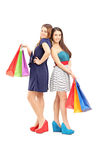 Full length portrait of two friends holding shopping bags Royalty Free Stock Photography