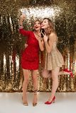 Full length portrait of two funny women in sparkly dresses. Full length portrait of two funny happy women in sparkly dresses taking a selfie while standing Royalty Free Stock Photos