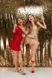 Full length portrait of two happy beautiful girls. In shiny dresses holding bottle of champagne and glasses while standing and celebrating isolated over golden Stock Images