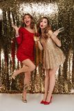 Full length portrait of two happy cheerful girls. In shiny dresses holding bottle of champagne and glasses while standing and celebrating isolated over golden Royalty Free Stock Photos