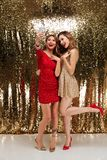 Full length portrait of two joyful attractive women. In sparkly dresses taking a selfie while standing and posing together isolated over golden shiny background stock photography