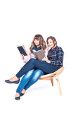 Full length portrait of two siting beautiful weman students holding books isolated on a white background. Full length portrait of two siting on chair beautiful Stock Photo
