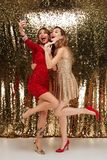 Full length portrait of two smiling laughing women in sparkly. Dresses taking a selfie while standing together and waving hands isolated over golden shiny Royalty Free Stock Images