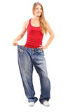 Full length portrait of a weigh loss female with old pair of jea Stock Photography