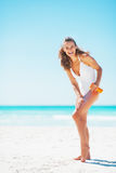 Full length portrait of woman applying sun screen creme Royalty Free Stock Images