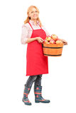 Full length portrait of a woman with apron holding a bucket full Royalty Free Stock Images