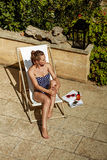 Full length portrait of woman in beachwear sitting in sunbed Stock Photos