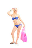 Full length portrait of a woman in bikini holding a bag Stock Photo