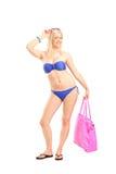 Full length portrait of a woman in bikini holding a bag Stock Photo