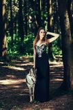 Woman in a black dress with a dog royalty free stock photo