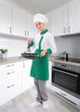 Full length portrait of woman chef in uniform holding frying pan Royalty Free Stock Image