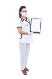 Full length portrait of woman doctor in mask holding clipboard w Royalty Free Stock Image