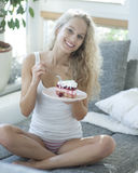 Full length portrait of woman having raspberry cake on sofa Royalty Free Stock Photo