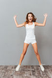 Full length portrait of a woman jumping with hands up Royalty Free Stock Photo