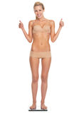 Full length portrait of woman in lingerie standing on scales Stock Photo