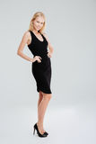 Full length portrait of a woman posing in black dress. Full length portrait of a beautiful cheerful woman posing in black dress with hands on hips isolated on a stock photo