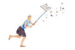 Full length portrait of a woman running and catching butterflies. With net isolated on white background royalty free stock images