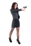 Full length portrait of woman shooting with gun isolated on whit Royalty Free Stock Images