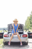 Full length portrait of woman sitting on convertible trunk against clear sky Royalty Free Stock Images
